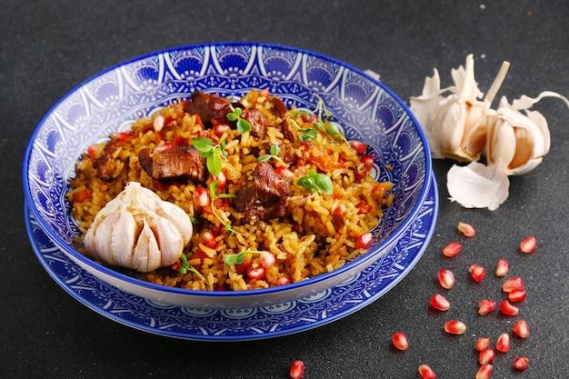 Pilaf en ingrediënten op plaat. nationale oezbeekse pilaf met vlees.