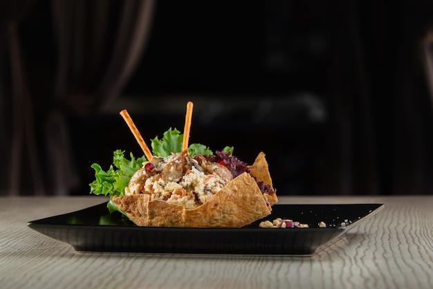 Pilaf in de vorm van gebakken pitabroodje, gegarneerd met broodstengels en sla op een zwarte vierkante plaat op een witte houten tafel.