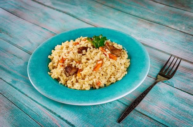 Pilaf met rijst, curry kruiden, wortel en vlees op blauw bord.