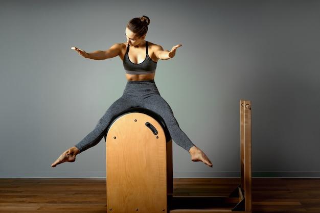Pilates, fitness, sport, training en mensenconcept - vrouw die oefeningen doet op een klein vat. correctie van het drijvende apparaat, correcte houding.