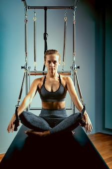 Pilates-hervormer bed, close-up, vrouw en instructeur die oefening doen op hervormersimulator voor behandeling van bewegingsapparaat