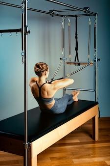 Pilates-hervormer bed, concept pilates-lichaamshormoon, vrouw en instructeur die oefeningen doen op de simulatorhervormer voor de behandeling van het bewegingsapparaat