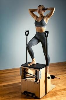 Pilates hervormer stoel vrouw fitness yoga gym oefening. correctie van het bewegingsapparaat, mooi lichaam. correcte houding.