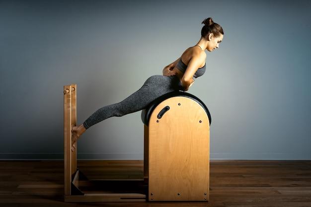 Pilates trainer oefeningen op een pilates vat. lichaamstraining, perfecte lichaamsvorm en houdingscorrectie opporno motorapparaat. ruimte kopiëren. vrouw die oefeningen op laddervat doet.