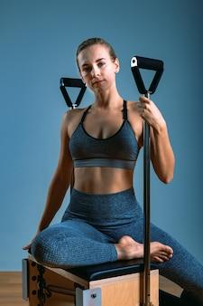 Pilates vrouw in een hervormer doen rekoefeningen in de sportschool. fitnessconcept, speciale fitnessapparatuur, gezonde levensstijl, kunststof. kopieer ruimte, sportbanner voor reclame.