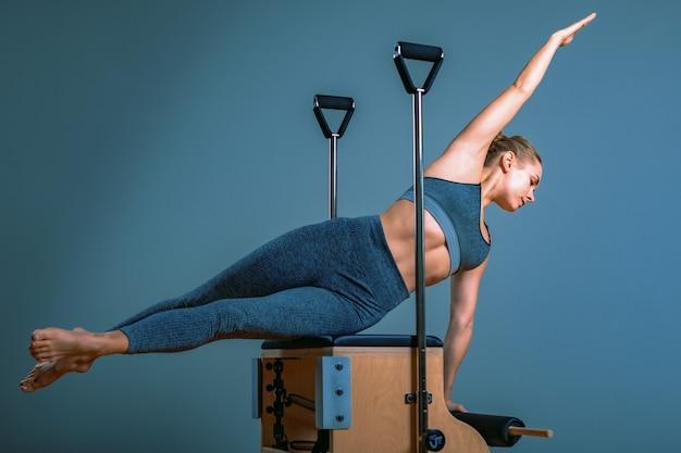 Pilates vrouw in een hervormer doen rekoefeningen in de sportschool