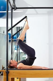 Pilates vrouw in hervormer toren oefenen op gymnasium