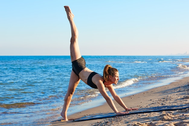 Pilates yoga workout oefening buiten op het strand