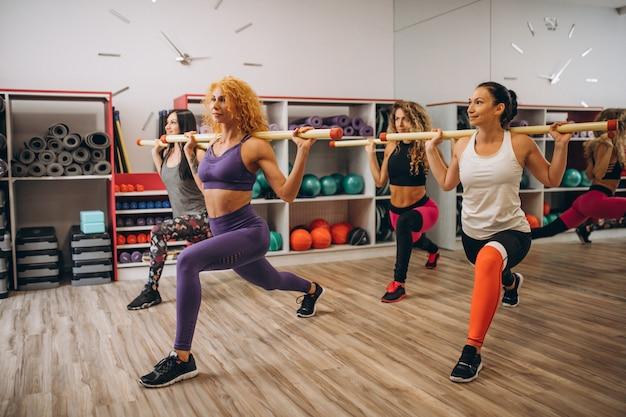 Pilatesgroep die in een gymnastiek uitwerkt