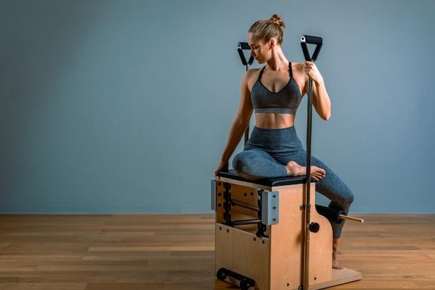 Pilatesvrouw in een cadillac-hervormer die rekoefeningen in de gymnastiek doet. fitnessconcept, speciale fitnessapparatuur, gezonde levensstijl, plastic. kopieer de ruimte, sport banner voor reclame