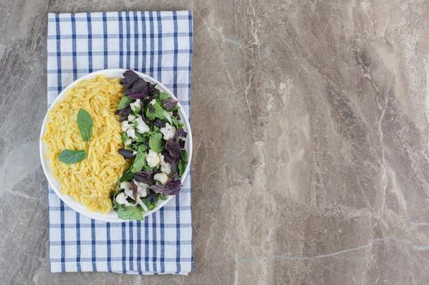 Pilau met smakelijke salade op een plaat op marmer.