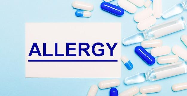 Pillen, ampullen en een witte kaart met de tekst allergy op een lichtblauwe achtergrond. medisch concept