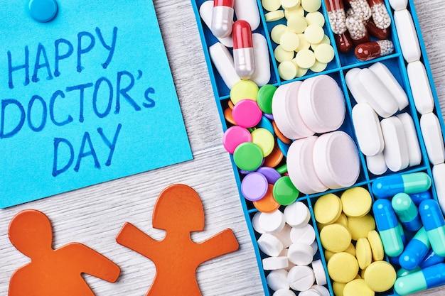 Pillen, capsules in een doos. stickmen op een houten achtergrond. viering van de dag van de dokter.