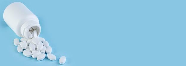 Pillen die uit witte fles op blauwe achtergrond met exemplaarruimte morsen. lange brede banner