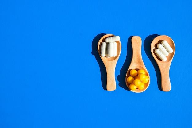 Pillen en capsules op houten lepels op blauwe achtergrond. hard licht en schaduwen. ruimte kopiëren. vitaminen prebiotica probiotica. dosis medicatie. gezondheidszorg.
