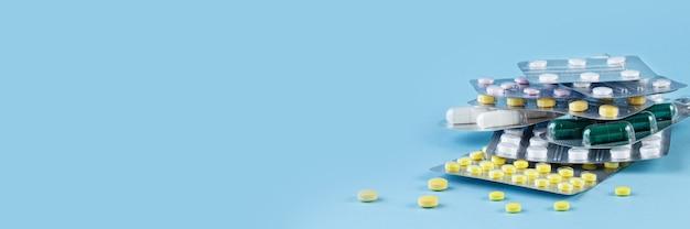 Pillen en capsules van verschillende kleuren op een blauw oppervlak