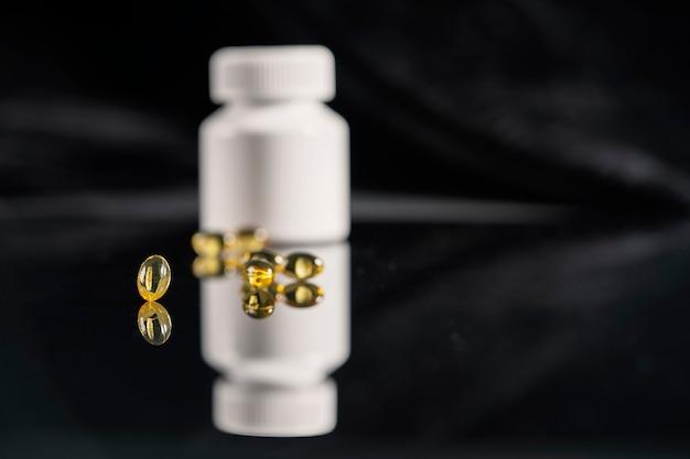 Pillen en een witte fles medicijnen liggen op een gespiegelde zwarte achtergrond, daarin weerspiegeld.