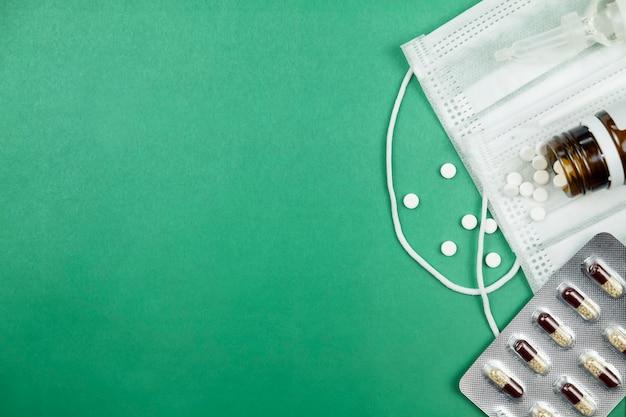 Pillen en geneeskunde masker op groene achtergrond met kopie ruimte. bovenaanzicht