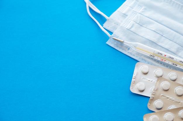 Pillen en medische beschermende maskers op blauwe achtergrond. kopieer ruimte