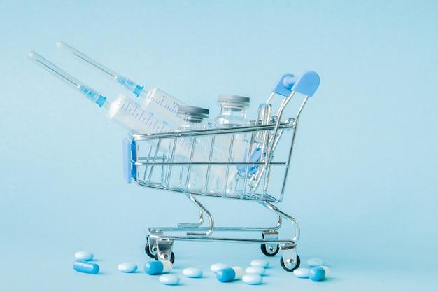 Pillen en medische injectie in winkelwagentje op blauw