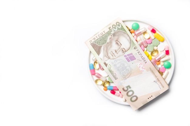Pillen en oekraïens geld op een witte achtergrond. het concept van de prijsstijging van drugs. plaats voor tekst