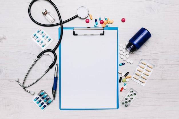 Pillen en stethoscoop rond klembord