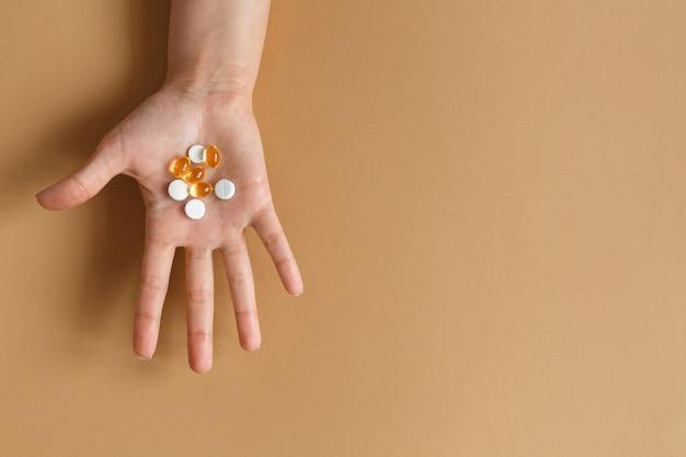 Pillen en vitamines in de palm van een vrouwelijke hand