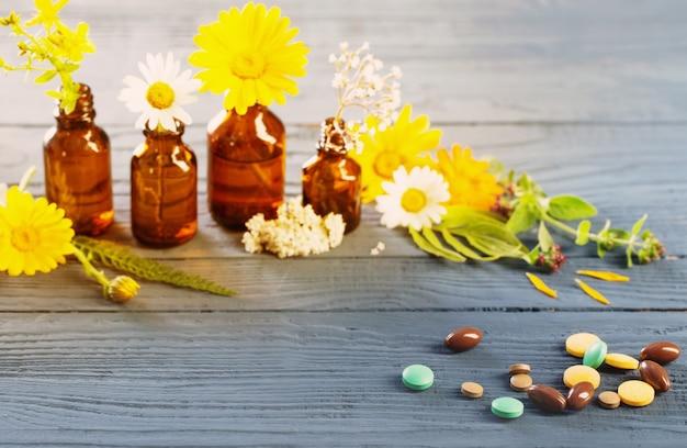Pillen en wilde planten op blauwe achtergrond, natuurlijke geneeskunde concept