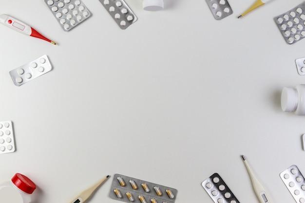 Pillen grens achtergrond vitaminen tabletten pillen thermometers op witte achtergrond bovenaanzicht kopie ruimte voor tekst