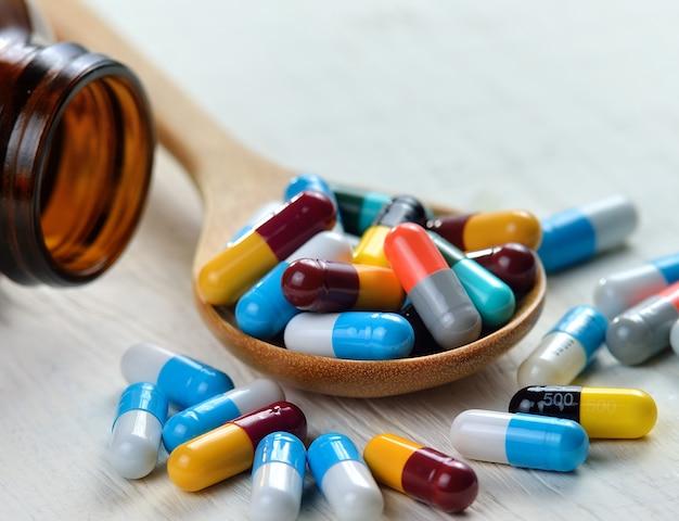 Pillen in de lepel op witte houten oppervlak