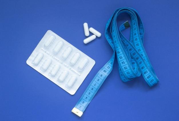 Pillen in een blaar en meetlint op een blauwe achtergrond