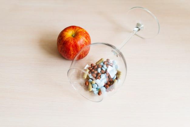 Pillen in een glazen kom en rode appel op een beige achtergrond. rijk aan vitamines.