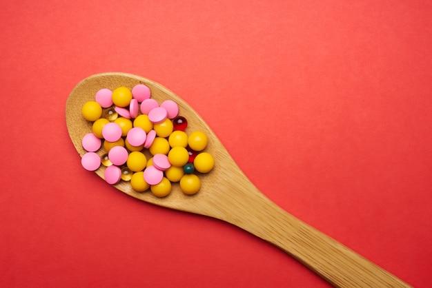 Pillen in een lepel op een rode achtergrond bovenaanzicht antibiotica geneeskunde