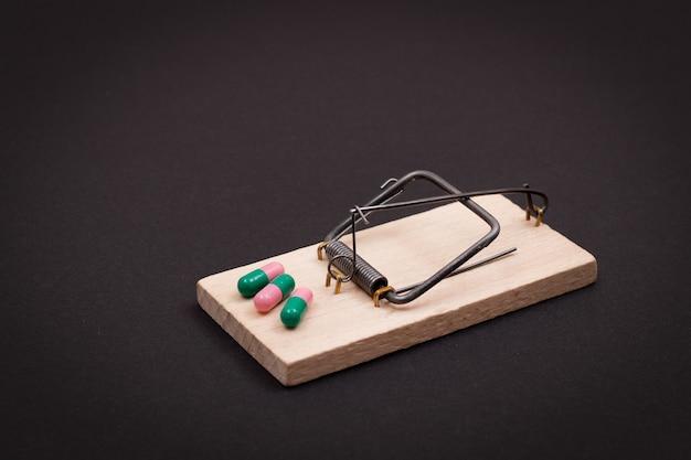 Pillen in houten muizenval farmaceutische verslaving