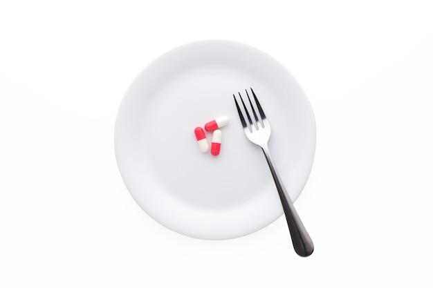 Pillen met vork op plaat geïsoleerd op wit, bovenaanzicht