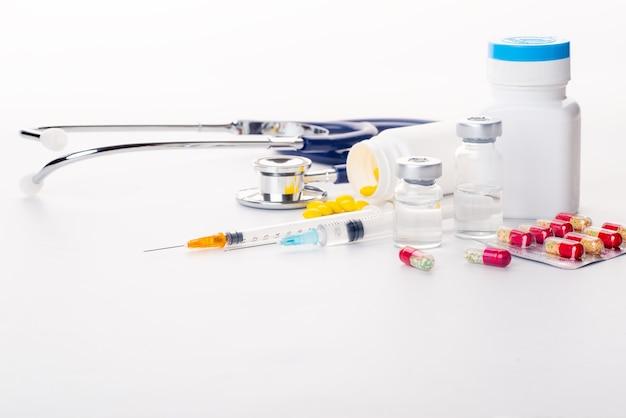 Pillen morsen uit pil fles spuit thermometer en stethoscoop op witte achtergrond