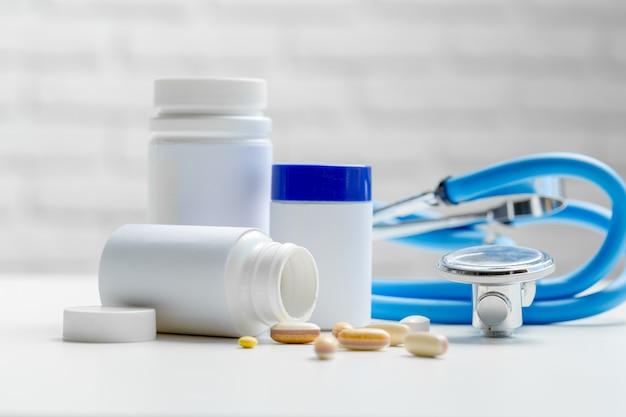 Pillen of capsules en stethoscoop op witte tafel