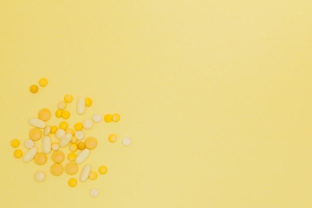Pillen op een gele achtergrond. concept ontwerp. pillen van een zonneschijn. zonnesteek. zomer ziekten achtergrond. kopieer ruimte