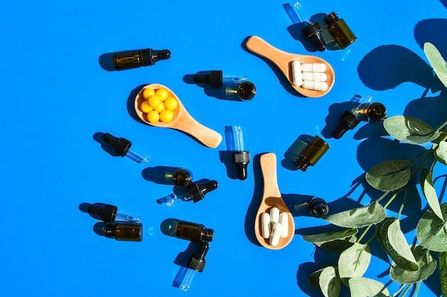 Pillen op houten lepel en druppelaar op blauwe achtergrond. hard licht en schaduwen. creatief minimalisme concept. vitaminen en prebiotica, probiotica. herfst vitamine dosis. eucalyptus