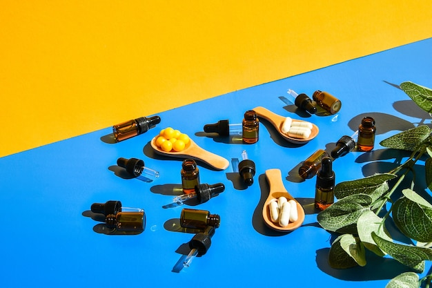 Pillen op houten lepel en druppelpipet op blauwe en gele achtergrond. hard licht en schaduwen. modern isometrisch creatief minimalisme concept. vitaminen en prebiotica, probiotica. herfst vitamine dosis.