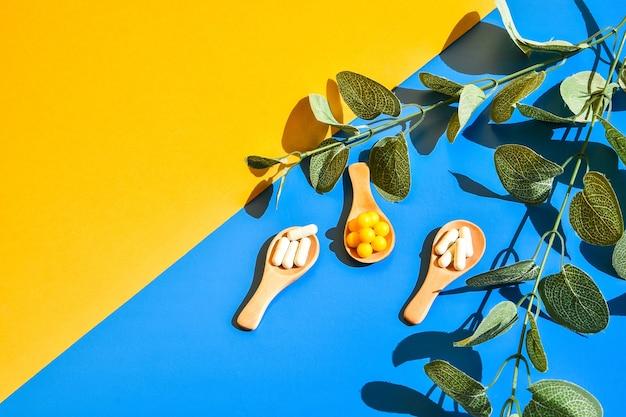 Pillen op houten lepel op blauwe en gele achtergrond. hard licht en schaduwen. modern isometrisch creatief minimalisme concept. vitaminen en prebiotica, probiotica. herfst vitamine dosis. eucalyptus