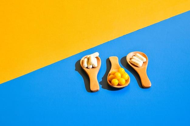 Pillen op houten lepel op blauwe en gele achtergrond. hard licht en schaduwen. modern isometrisch creatief minimalisme concept. vitaminen en prebiotica, probiotica. herfst vitamine dosis.