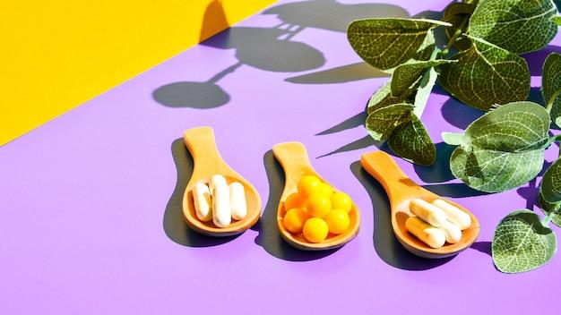 Pillen op houten lepel op paarse en gele achtergrond. hard licht en schaduwen. modern isometrisch creatief minimalisme concept. vitaminen en prebiotica, probiotica. herfst vitamine dosis. eucalyptus