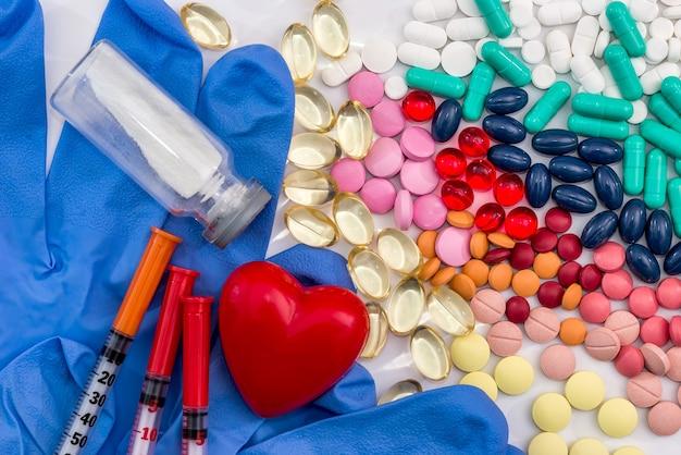 Pillen, spuit, medische handschoenen, ampullen en hart