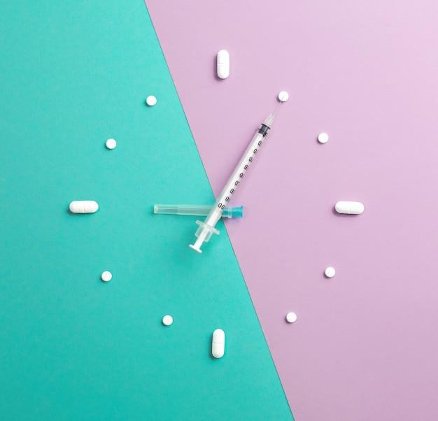 Pillen, tabletten en spuit in de vorm van horloge op kleurrijke achtergrond. medisch en gezondheidsconcept in minimalistische stijl. bovenaanzicht.