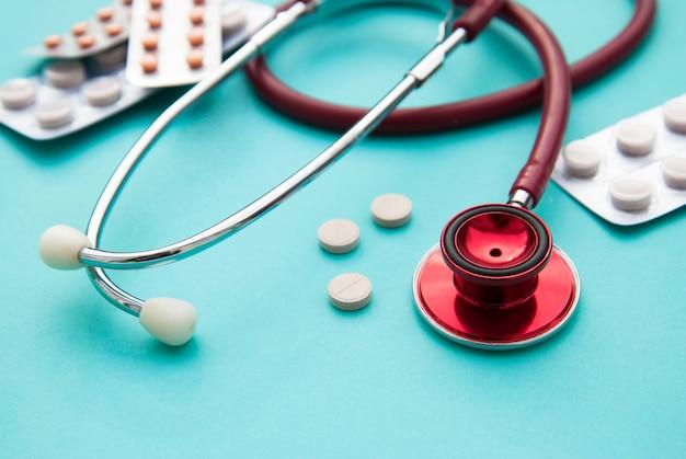 Pillen, tabletten en sthetoscope op blauw. gezondheidszorg en medicijnen. copyspace.