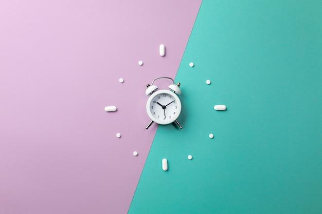 Pillen, tabletten en witte wekker op groen en paars