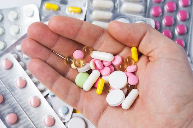 Pillen, tabletten, vitamines en drugs stapelen zich op in volwassen handen, close-up weergave.