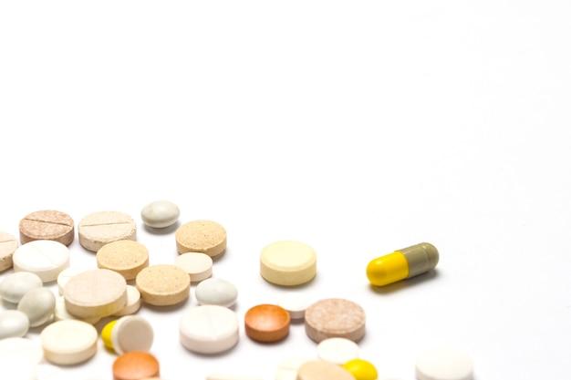 Pillen van verschillende maten en kleuren en op een witte geïsoleerde achtergrond. concept van de farmaceutische industrie, dagelijkse vitamines en mineralen voor vrouwen. zwangerschap, menopauze