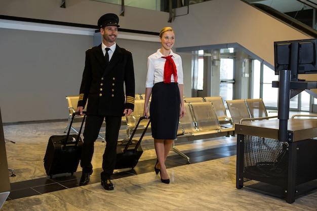 Piloot en stewardess lopen met hun trolleytassen